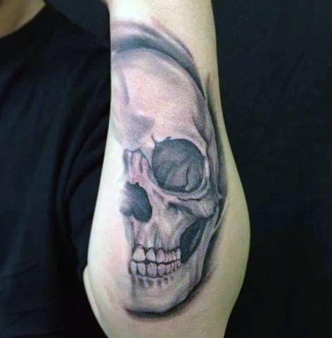 half skull forearm tattoo