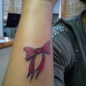 tatuaż kokardai serce na przedramieniu