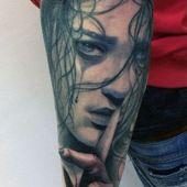 forearm face tattoo
