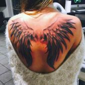 woman wings on back tattoo
