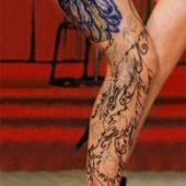 tatuaże paw na udzie kobiety