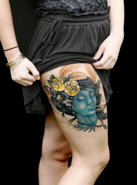 tatuaże na udzie twarz i róże